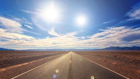 Fiktive Darstellung einer Landstraße durch die Wüste mit zwei mittig zum Betrachter strahlenden Sonnen am Himmel. Wolken am blauen Himmel. Leicht dramatische Stimmung.
