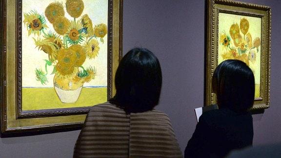 Besucherinnen einer Ausstellung betrachten zwei Sonnenblumen-Gmälde von Vincent van Gogh