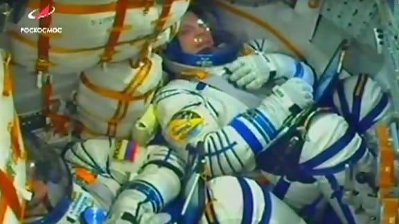 In einer Kapsel liegen zwei zusammengekauerte Menschen in Raumanzügen