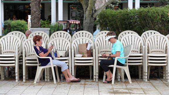 Zwei Frauen sitzen sich mit großen Abstand gegenüber