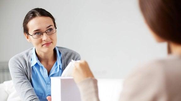 Eine Frau gibt jemandem eine Schachtel Taschentücher