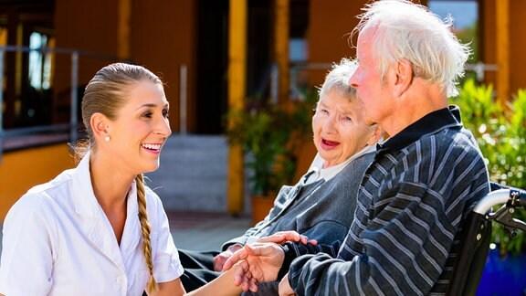 Eine Pflegerin mit einem älteren Pärchen im Rollstuhl