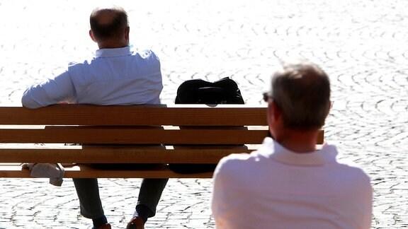 Zwei Männer sitzen einzeln auf zwei Bänken mit großem Abstand zueinander
