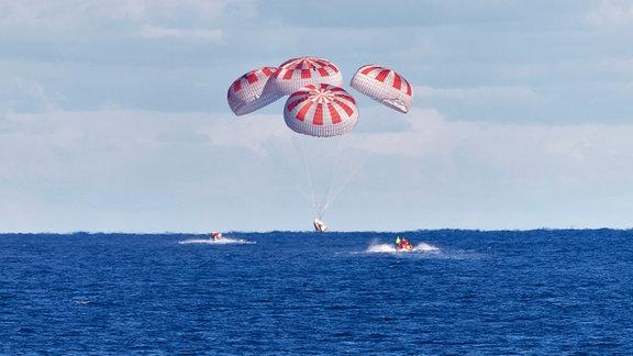Die Crew Dragon von SpaceX wird von vier Fallschirmen geführt, als sie am 8. März 2019 nach der Rückkehr des unbemannten Raumschiffs von der Internationalen Raumstation im Rahmen der Demo-1-Mission in den Atlantik eintaucht.