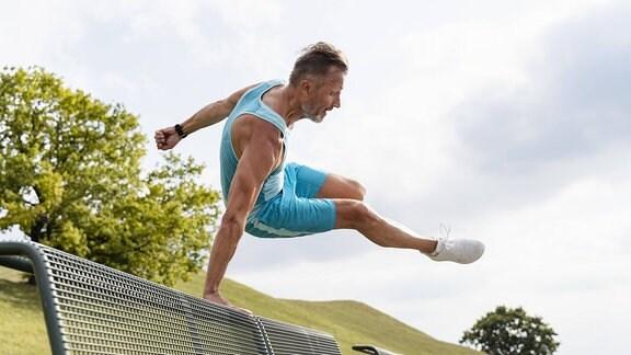 Sportler springt über Parkbank