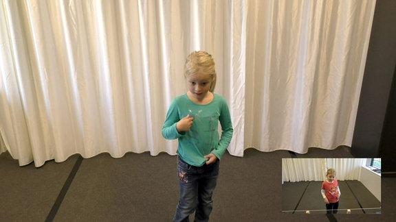 Kind steht auf Boden und zieht an seiner Kleidung.