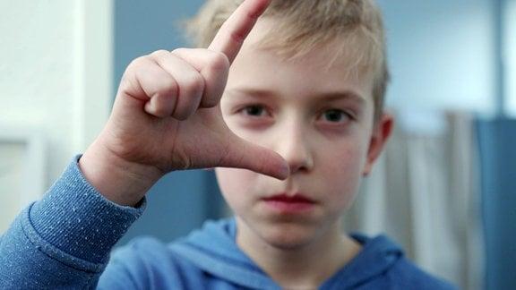 Kind macht ein Zeichen mit der Hand.