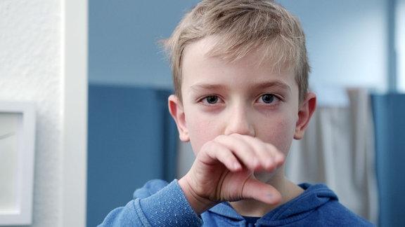 Kind wischt mit Handrücken über Mund.