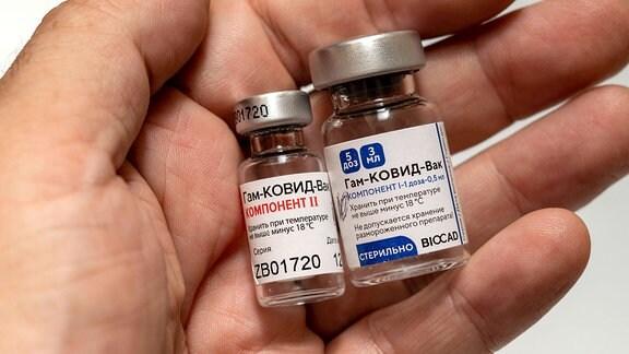 Zwei Ampullen mit dem Sputnik-V-Impfstoff auf einer Handfläche
