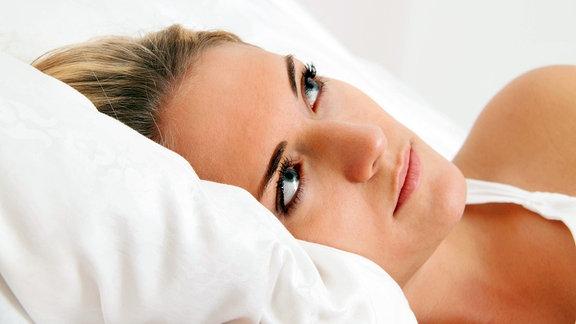Eine junge Frau liegt mit offenen Augen im Bett.