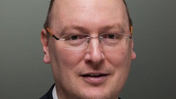 Porträtaufnahme eines mittelalten weißen Mannes mit sehr kurzen Haaren und einer Brille.