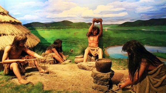 Ein Bild zeigt Steinzeitmenschen bei der Arbeit.