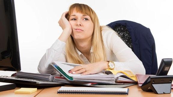 Eine Frau hängt gelangweilt am Schreibtisch rum.