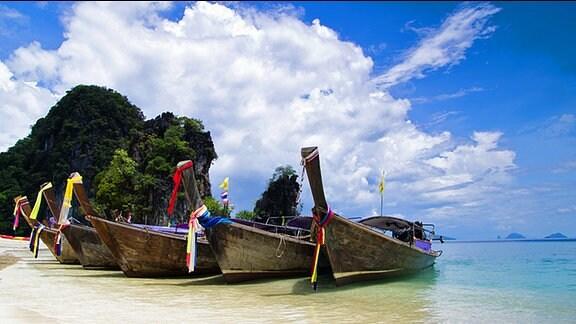 Mit bunten Fähnchen geschmückte Boote liegen an einem tropischen Strand