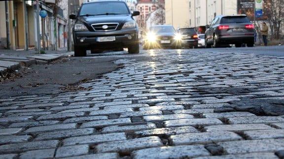 Die Dieskaustraße in Leipzig, im Vordergrund ist ein mit Kopfsteinen gepflasterter Streifen zu sehen, der nach vielen jahren ohne Sanierung ziemlich uneben geworden ist.