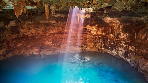 Innenaufnahme einer Höhle mit erdigen Wänden und einer bemoosten Decke, in die ein Loch klafft. Durch dieses Loch fällt Sonnenlicht auf den klaren Süßwassersee am Boden der Höhle.