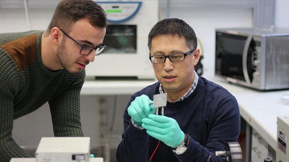 Zwei Forscher betrachten einen Kondensator in einem Labor