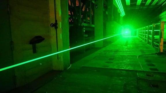 Eine Betontunnel, durch den ein grün leuchtender Laser geschossen wird.