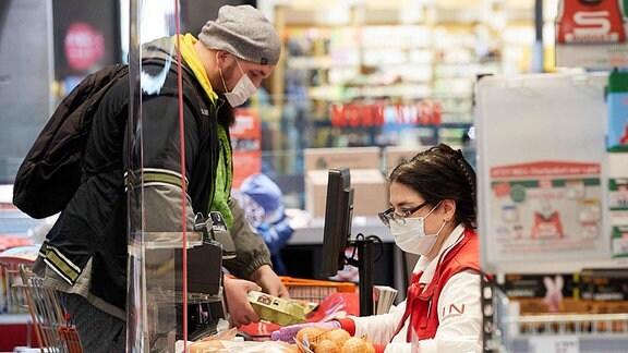 Ein Mann steht an einer Kasse im Supermarkt. Käufer und Verkäuferin tragen Mundschutz.