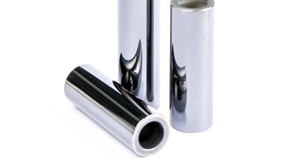 Drei zylinderförmige, glänzend silberne Röhrchen - Kolbenbolzen - stehen nebeneinander.
