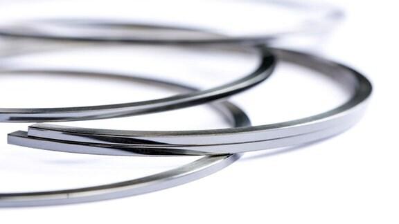 Mehrere silber-farbene Ringe - sogenannte Kolbenringe - liegen übereinander.