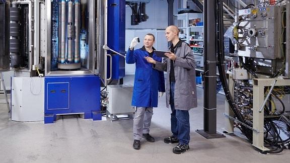 Zwei Männer in Labor-Arbeitskleidung stehen vor technischen Geräten und blicken auf eine zylinderförmige Röhre, die einer der beiden in der Hand hält. Der andere Mann hält ein Tablet in der Hand.