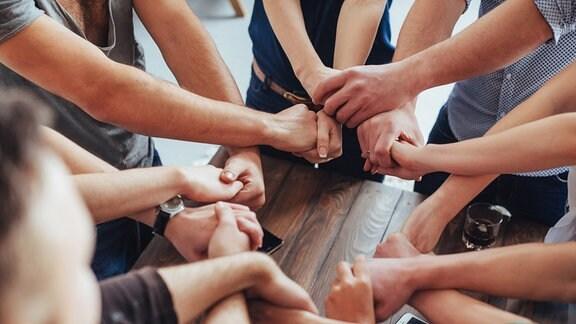 Acht Personen stehen im Kreis und fassen sich über Kreuz an die Hände.