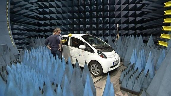 Absorberkammer mit vielen Spitzen an Wand und Boden, darin ein kleiner PKW und zwei Personen an einem Funkwellenmessgerät