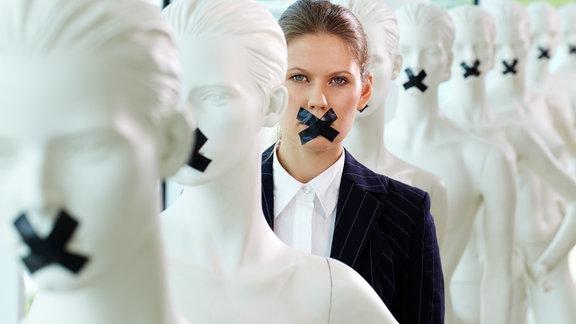 Frau und Schaufensterpuppen stehen mit zugeklebten Mündern in einer Reihe
