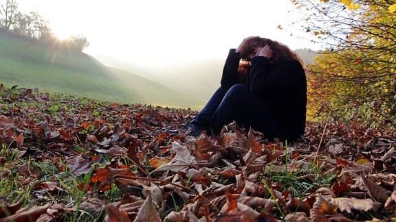 Unglückliche Frau sitzt im Herbstlaub