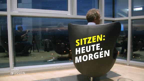 """Drehsessel umgedreht, vor hohen Fenstern in Hochhaus, darauf Schrift """"Sitzen: heute, morgen"""""""