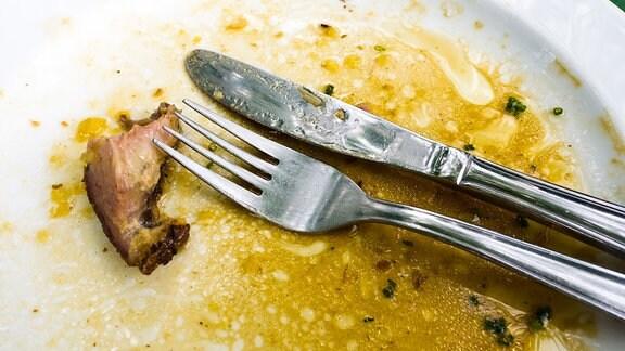 Besteck und Essensreste auf einem Teller