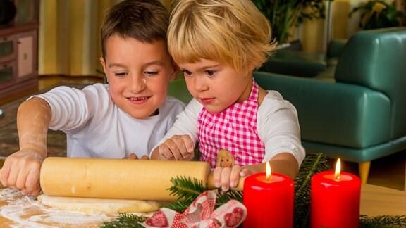 Kinder backen Weihnachtsplätzchen.