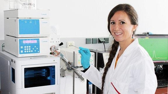 Eine Frau in weißem Laborkittel steht vor einem Apparat mit einer Injektionsadel