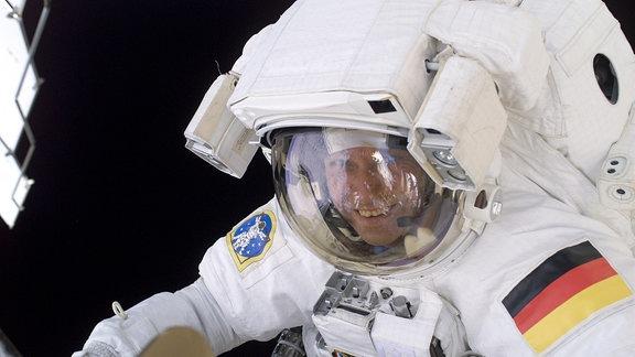 Der Raumfahrer Thomas Reiter bei einem Außeneinsatz im Raumanzug, lächelnd