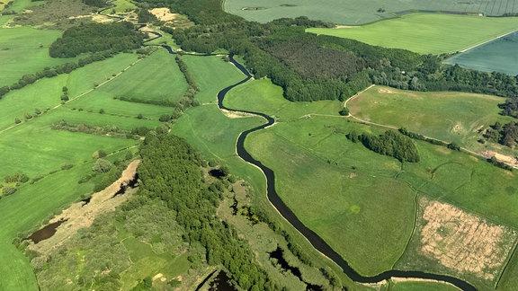 Ein Fluss schlängelt sich durch eine grüne Landschaft