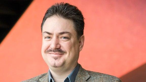 Porträt von Mann mit freundlichem Gesicht, kürzern, nach oben aufgestellten, dunklen Haaren, Oberlippen- und leichtem Kinnbart.