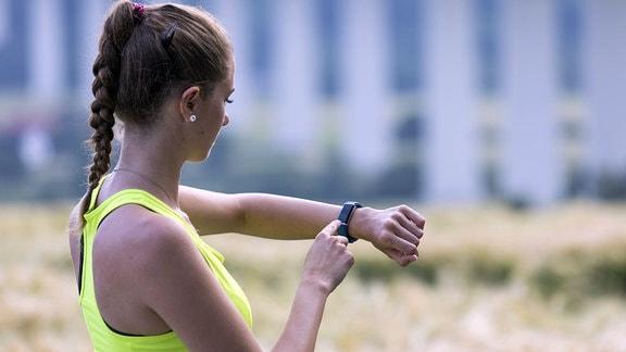 Eine junge Frau beim Joggen kontrolliert ihre Vitaldaten auf einer Fitness Uhr