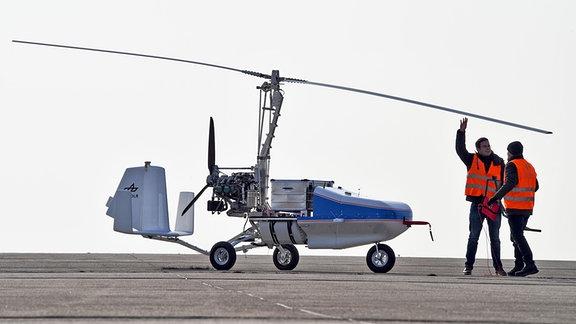 Forscher stehen neben dem Prototyp eines unbemannten Tragschraubers, der als Drohne für Fracht konzipiert ist.