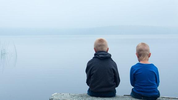 zwei Kinder sitzen am Wasser