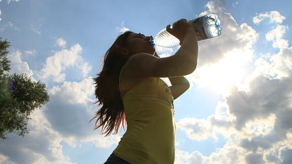 Frau mit dunklen, im Wind wehenden Haaren trinkt aus einer Wasserflasche, Foto aus Froschperspektive