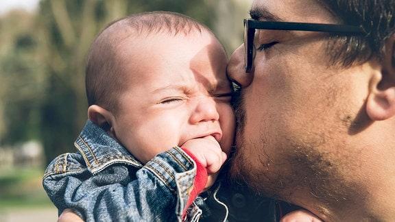 Mann tröstet sein weinendes Kind