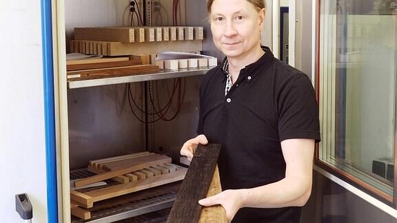 Wissenschaftler Zauer mit Holz in den Händen vor einer Kammer, in der er das Holz testet