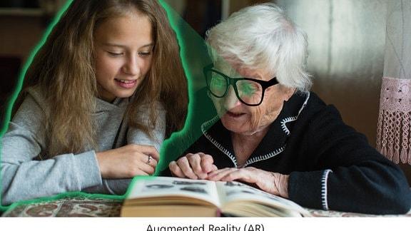 Seniorin sitz mit einem Roboter am Tisch und liest in einem Buch. Auf das Display des Roboters ist ihre Enkelin zu sehen.