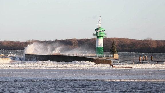 Sturmflut über der Nordermole mit Leuchtturm