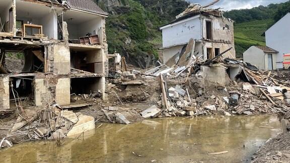 Ruinenartige Fasseaden mehrstöckiger Häuser mit Wasser im Vordergrund und Felsen sowie Weinberg im Hintergrund.