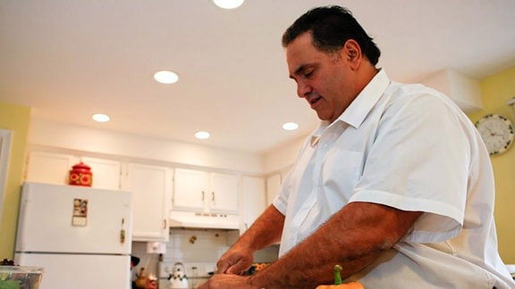 Übergewichtiger Mann schneidet Gemüse in einer Küche.