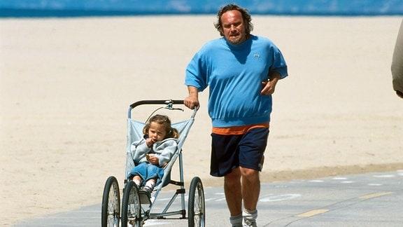 Übergewichtiger Vater schiebt einen Babyjogger