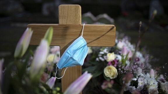 An einem Grabkreuz hängt ein Mund-Nasen-Schutz.