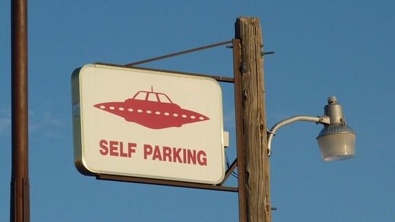 """Schild an Laternenpfahl mit UFO-Piktogramm und Aufschrift """"Self Parking"""""""